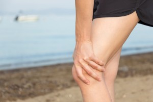 Jogger woman is holding her injured knee during jogging.